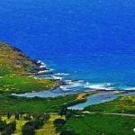 Na zdjęciu widać zielone wybrzeże wyspy Oahu. Wybrzeże przecina droga a za nią widać błękitne zatoczki