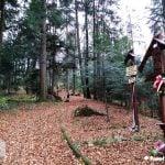 Szlak biegnący wzdłuż drogi krzyżowej. Na zdjęciu drewniane rzeźbione stacje drogi krzyzowej. W woddali zielony las.