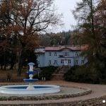 Ciekawy architektonicznie budynek sanatorium w Rymanowie Zdrój. Na pierwszym planie fontanna.