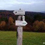 Drogowskaz szlaku: Czy zobaczymy Tatry?. W tle lasy i góry