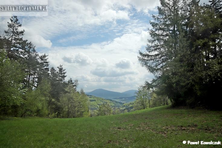 Punkt widokowy w Beskidach. Piekne białe chmury pokrywjące zieloną polanę.