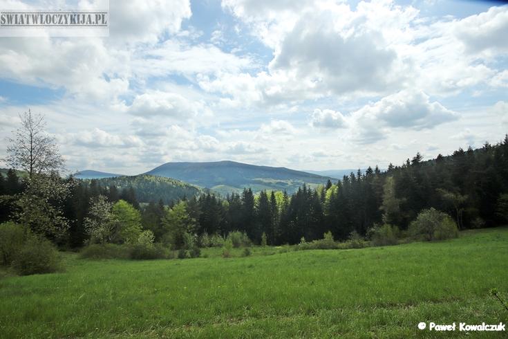 Beskidy - panorama. Łąka, las i góry. Nad nimi góróją białe obłoki
