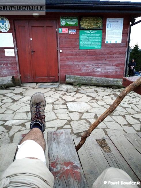 Schronisko na Luboniu Wielkim. Na pierwszym planie zabandażowane kolano i kij. Beskidy.