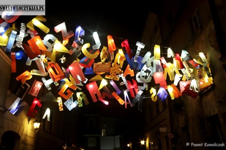Kolorowe litery podświetlone światłe. Zawieszone pomiędzy kamienicami nad ul. Złotą.