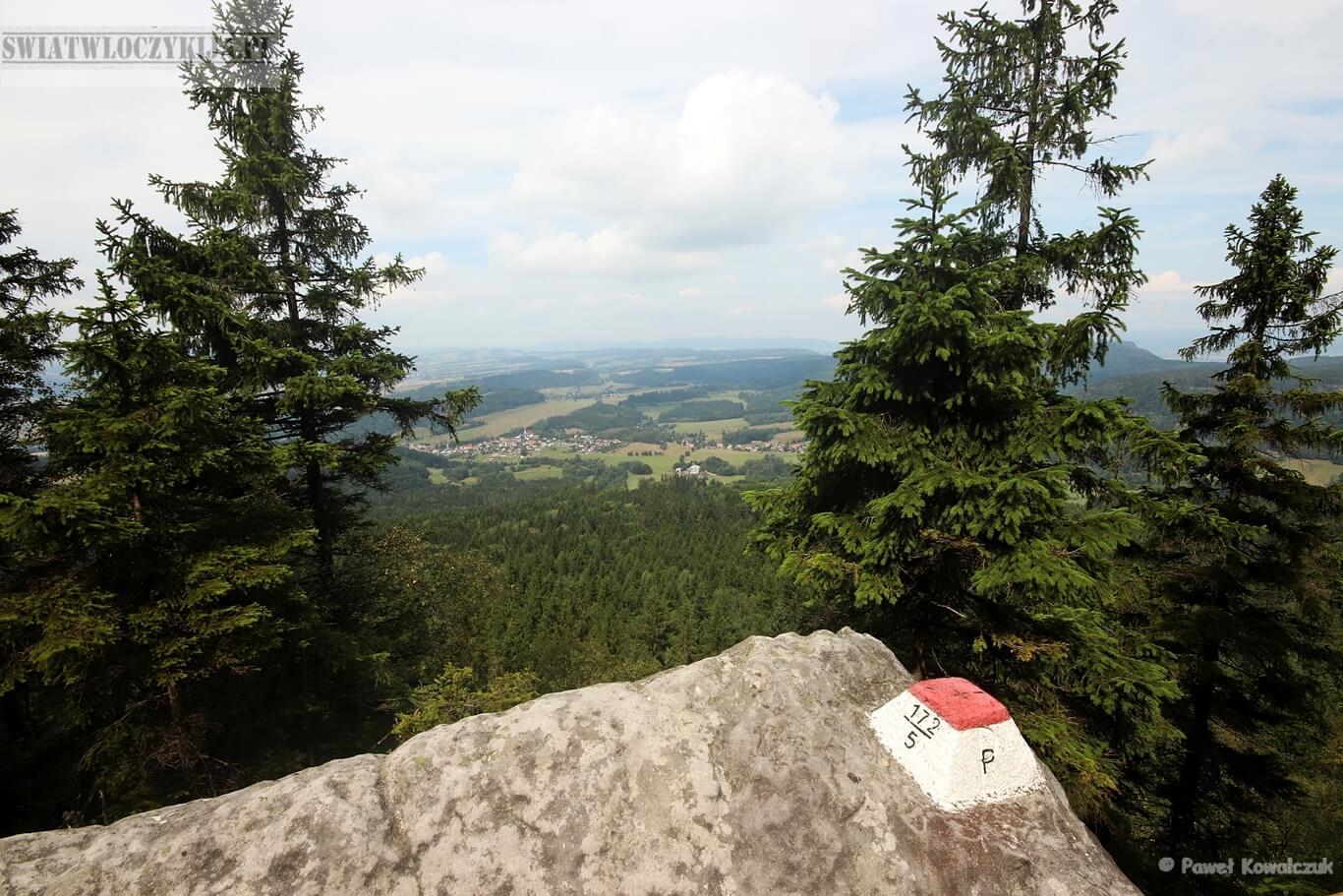 Widok na czeską stronę z Błędnych Skał. Na pierwszym planie kamień graniczny na skale. W tle panorama.
