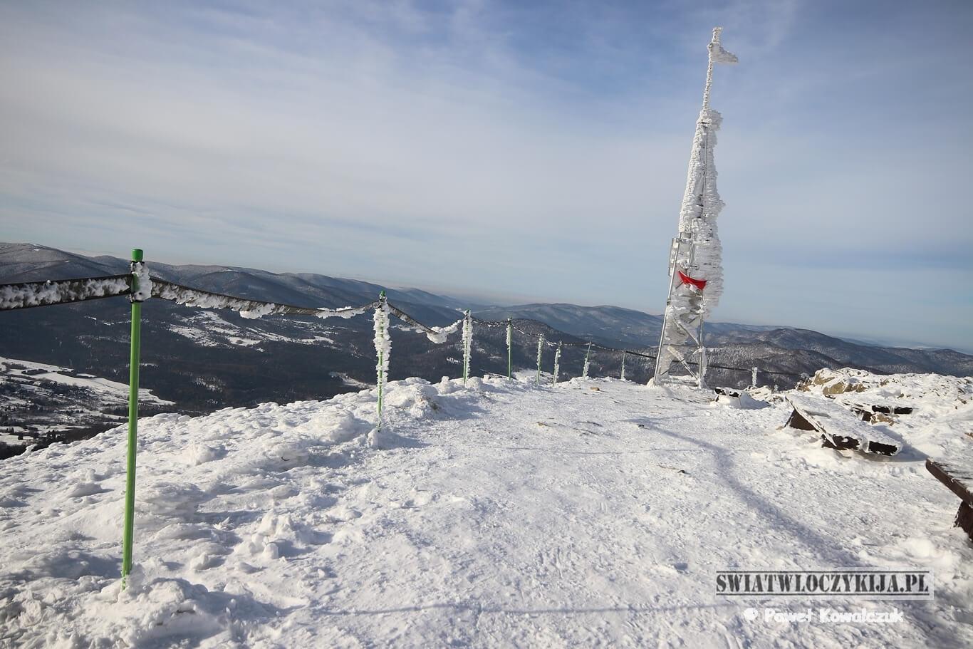 Bieszczady - krzyż na szczycie góry Smerek. Na zdjęciu oblodzony krzyż. W tle góry i śnieg.