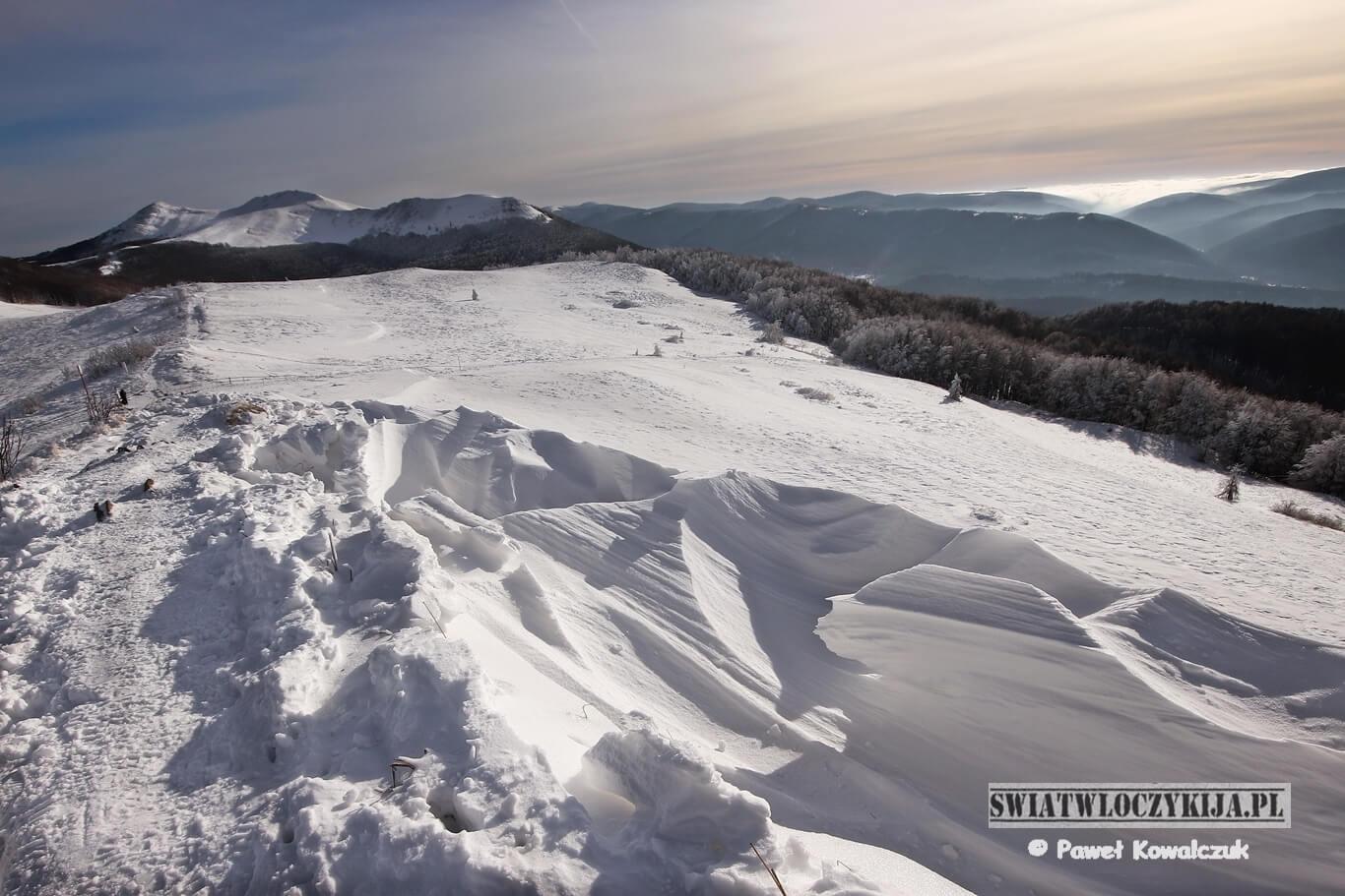 Bieszczady - widok ze szczytu Smerek. Na pierwszym planie wyżłobiony przez wiatr śnieg. W tle pasma Bieszczad.