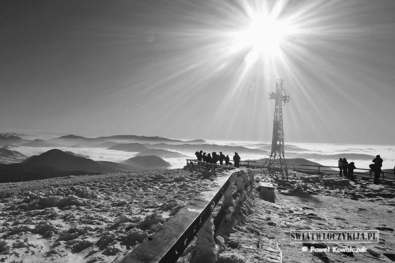 Tarnica - najwyższy szczyt Bieszczad. Zdjęcie w odcieniach szarości. Ukazuje barierkę drewnianą ciągnącą się do Krzyża nad którym góruje rozświetlone słońce. Pod krzyżem widać grupke ludzi wpatrujących się w okalające szczyt morze chmur.