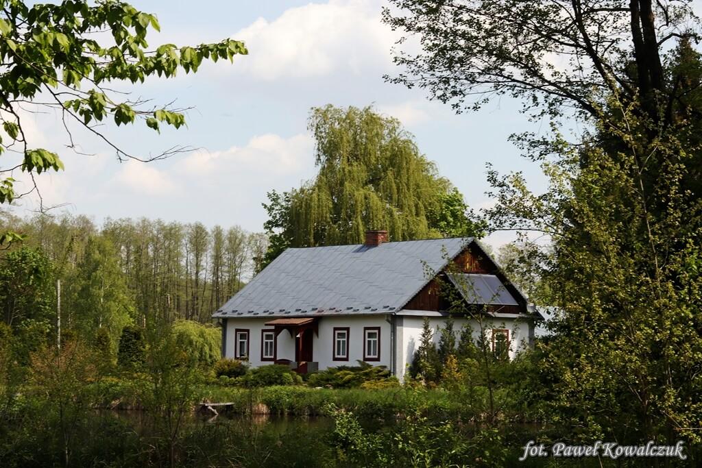 Zabytkowy domek nad stawem otoczony zieloną roślinnością